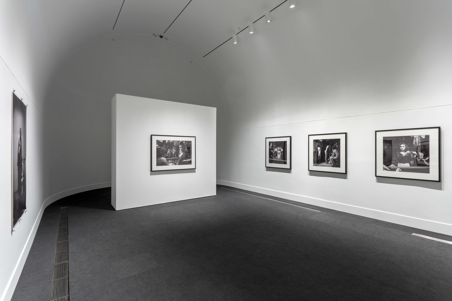 A white gallery with a curved back wall with three black and white photographs hanging on the far wall, one hanging on the wall to the left, and one on a free-standing wall near the back of the room.