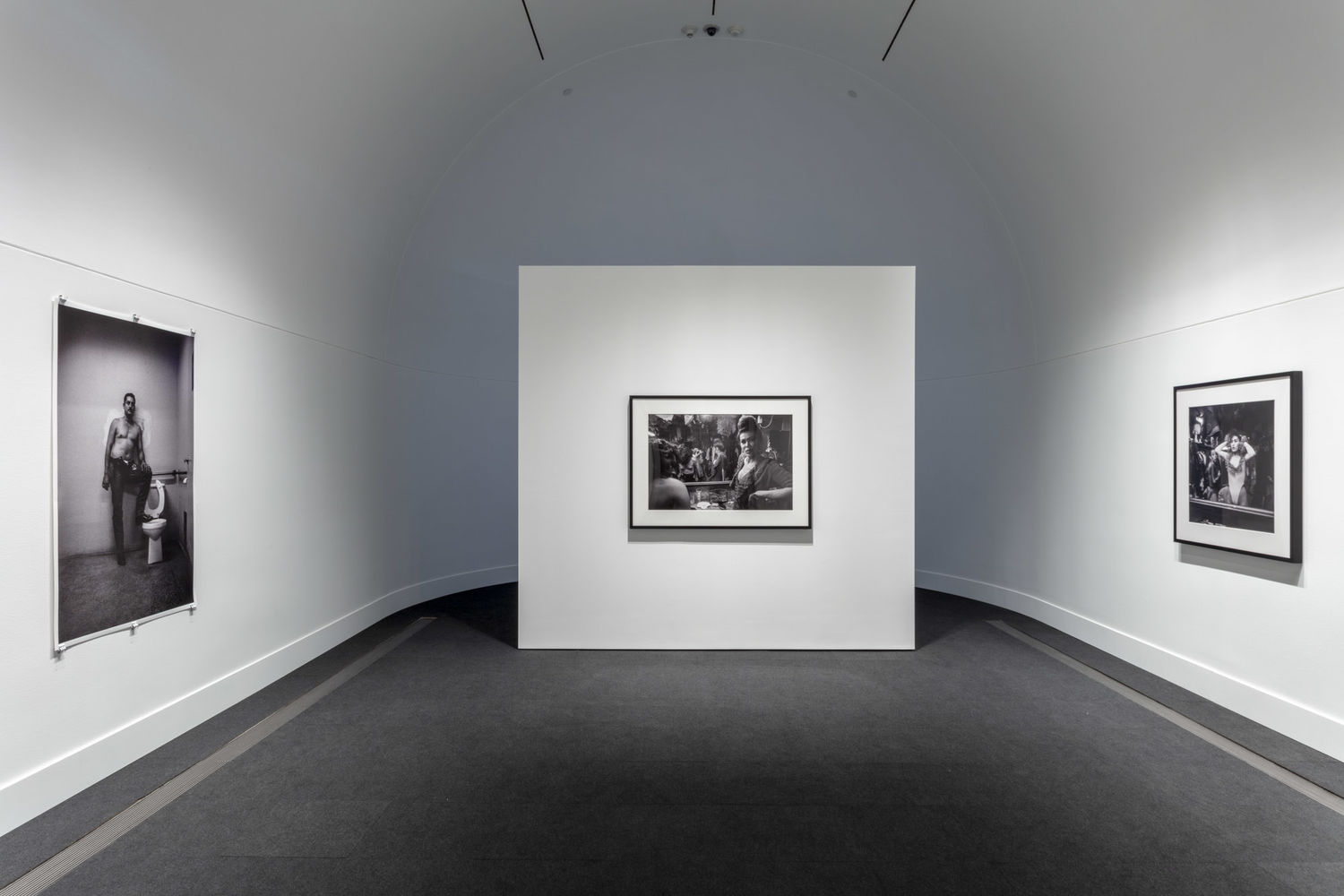 A white gallery with a curved back wall with one black and white photographs hanging on the wall at right, one hanging on the wall to the left, and one on a free-standing wall near the back of the room.