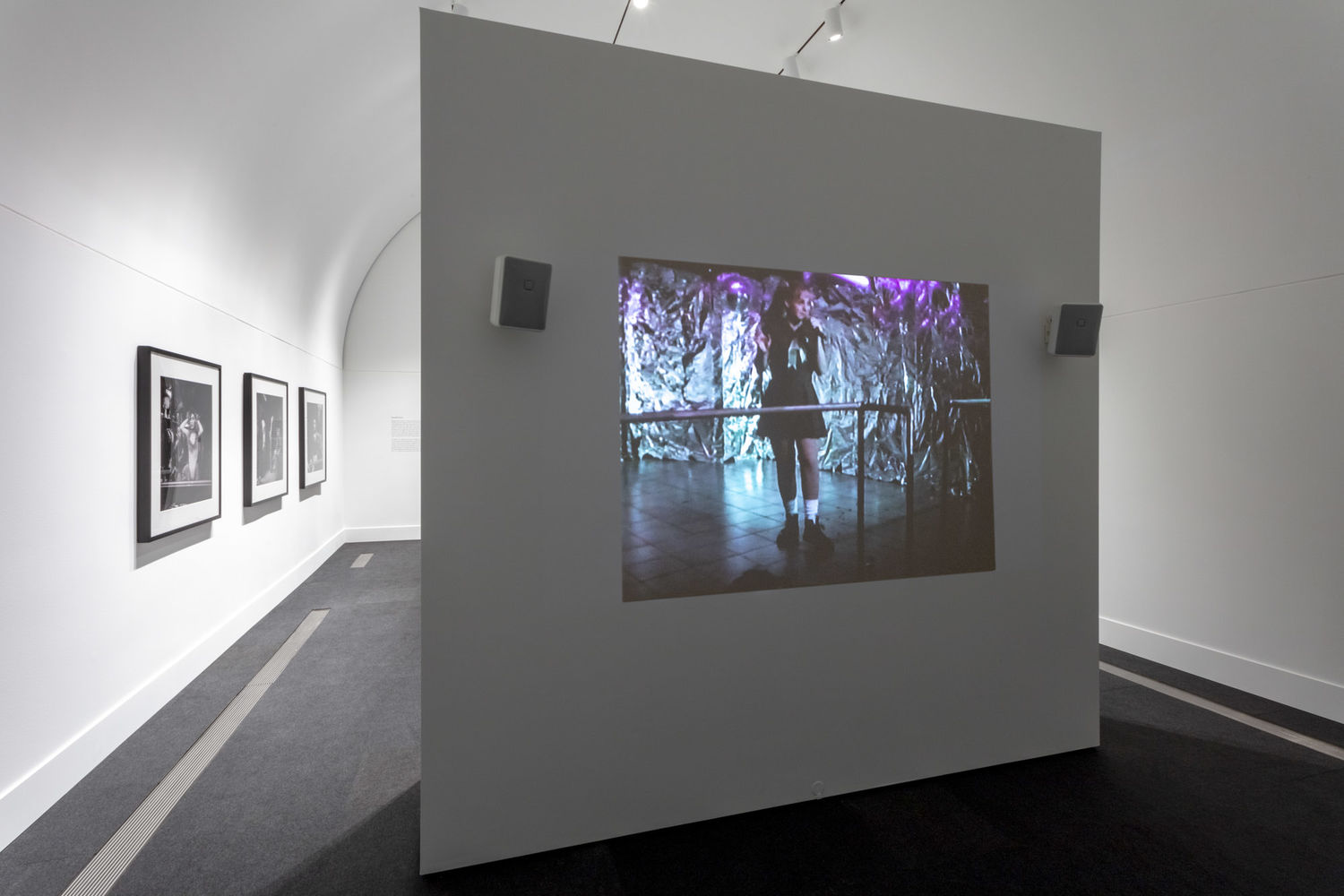 A white gallery with a free-standing wall standing in the foreground. A projection of a color image is visible on the free-standing wall. Three black and white photographs are visible on the gallery walls to the left in the background.