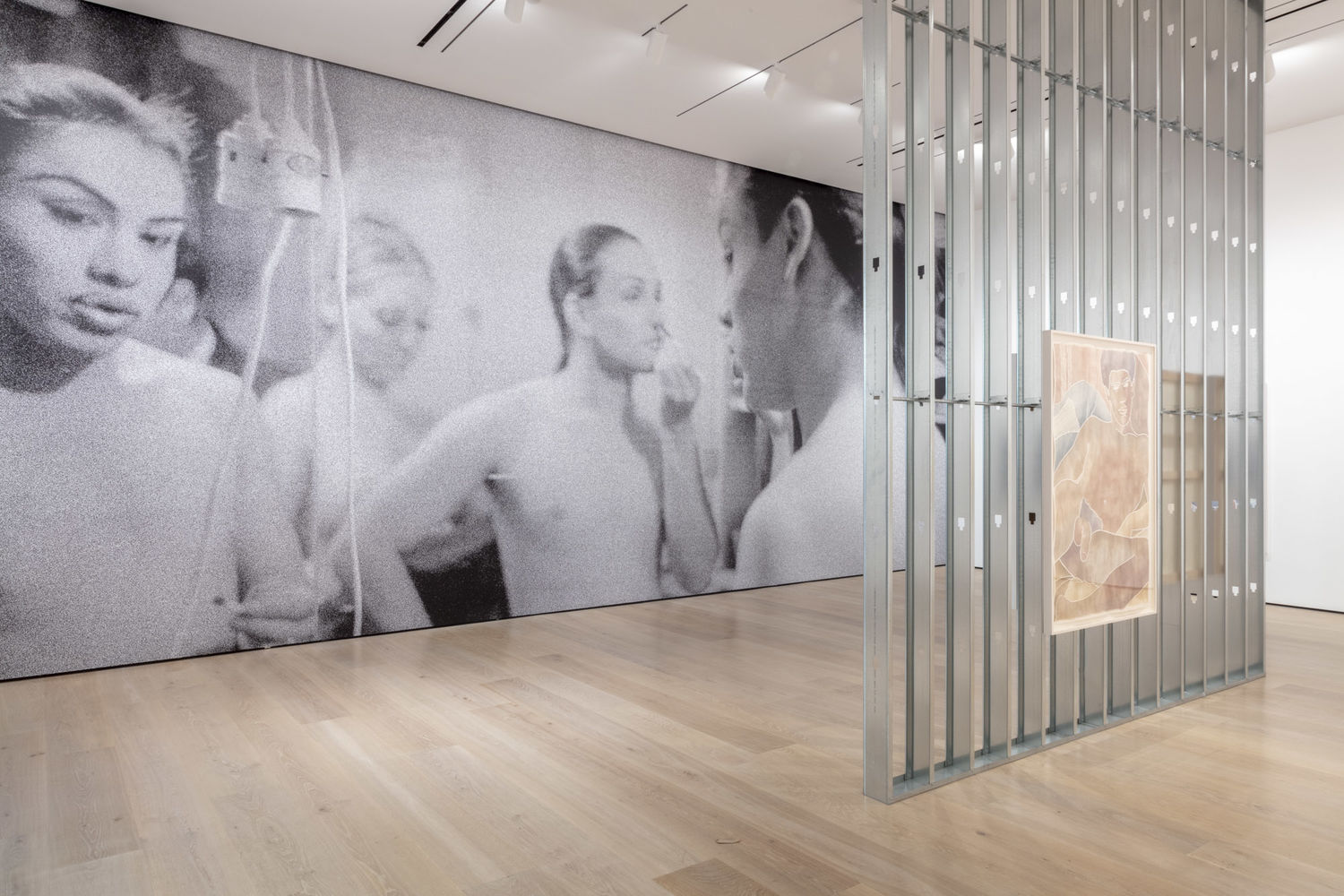 A large gallery with a black and white floor-to-ceiling photomural on the back wall. In the mural, four people are visible from the waist up with hair tied back. One is applying makeup. A power cord hangs across the foreground on the left. In the foreground of the gallery is a wall of metal studs with an arwork of muted colors hanging on it.