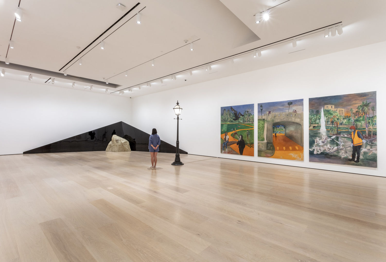 A gallery with a black streetlamp in the middle that divides two works. To the right is a triptych of paintings displaying MacArthur Park in Los Angeles. To the left is a dark, triangular shape that extends across corner of the room, with the peak of the object in the corner/center. A large rock sits on the floor in front of the triangle. A person stands to the left of the streetlamp.