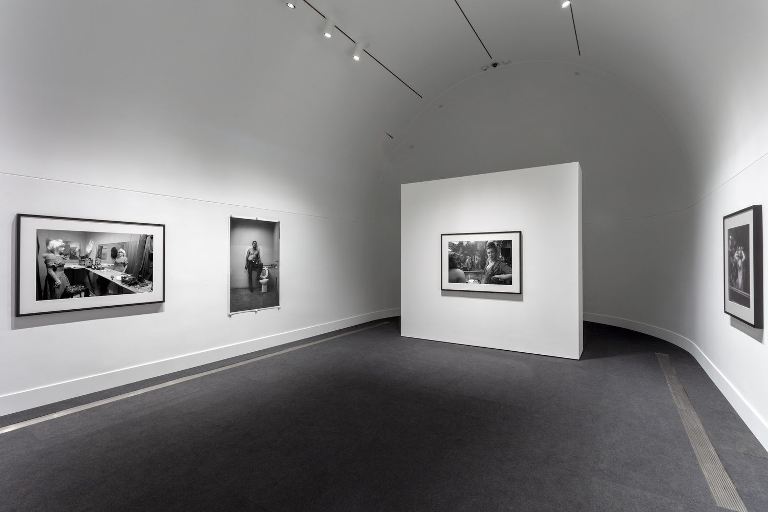 A white gallery with a curved back wall with one black and white photograph hanging on the central, freestanding wall, two black and white photographs on the left wall, and one photograph on the right wall.