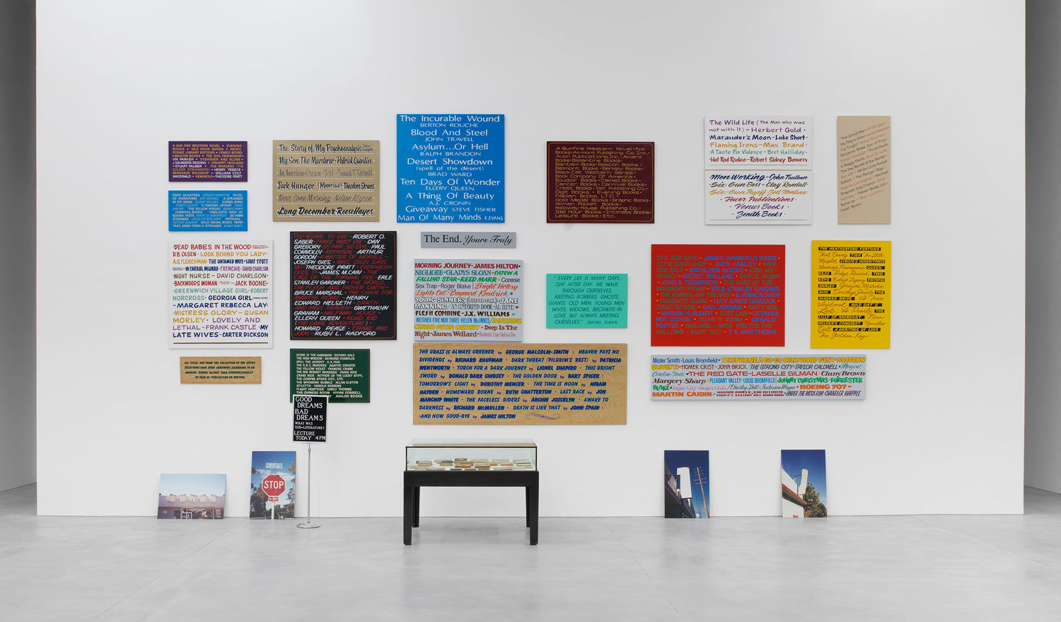 Allen Ruppersberg, Good Dreams, Bad Dreams (What Was Sub-Literature?), 1996. Mixed-media installation with nineteen hand-painted signs, stanchion sign, four color photographs, forty books from the artist's collection. Collection Aïshti Foundation, Beirut; Installation view of the exhibition Good Dreams, Bad Dreams,: American Mythologies; photo: Guillaume Ziccarelli.