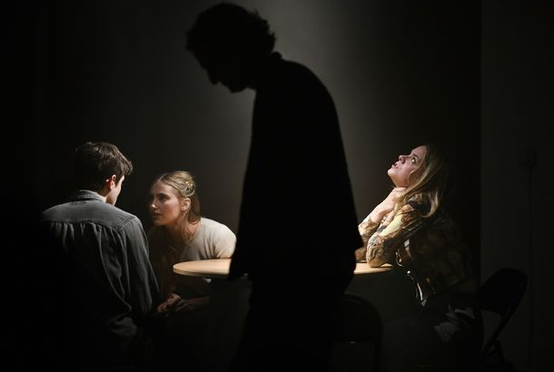 Three people at a table with the silhouette of a figure in front