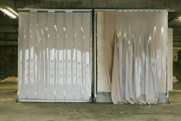 Two plastic curtains hang from standing racks