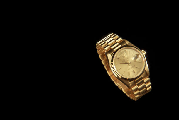A gold watch on a black background