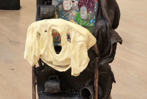 A sculpture with an combination of an upright steel folding chair encased within a tower of five tires  cut in half.  A butter yellow ceramic shirt is draped over the folded steel chair.