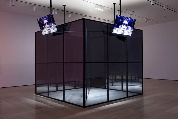 A large, mirror-like cube in the middle of a gallery, with television screens along each side