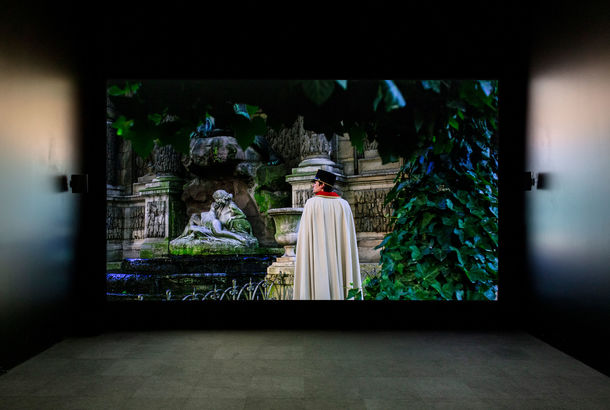 A screening room with an image of a caped man standing in a garden