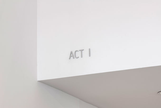 "View of white walls and an architectural overhang, with the words ""ACT I"" set in thin grey three-dimensional letters on the overhang."