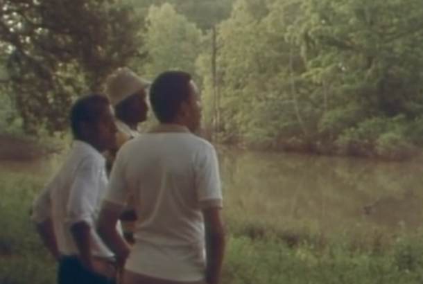 Rectangular image of three black men standing on a grassy, green riverbank. The brownish river splits the image in three, with the other side of the riverbank filled with trees. The men stand in a line, with the middle and far right men fully visible and the head of the far left man visible. That man has a cream white hat on. The two men we can see have their arms on their hips. We cannot see their legs.