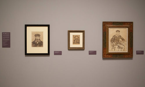 A gallery wall with three Van Gogh works on paper hung on it, and didactic labels. The wall is painted a neutral brown grey and the prints are all dark brown lines on parchment colored paper.