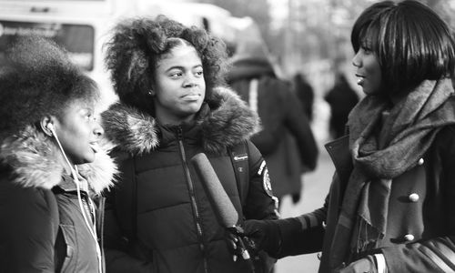 Two young women in coats face a woman holding a microphone