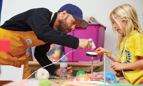 A girl in a yellow shirt is holding up an art project and is assisted by a man in a baseball cap who leans over with a glue gun pointed at the girl's project.