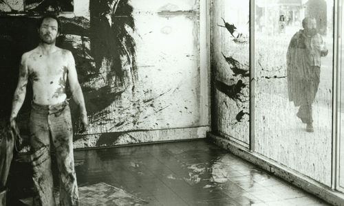 A man stands shirtless before a glass wall