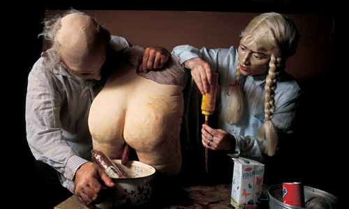 Two people wearing doll-like masks lean over a table where a nude bottom that appears made from plaster or papier-mache is sitting,  Various bowls and pots sit on the table as well.