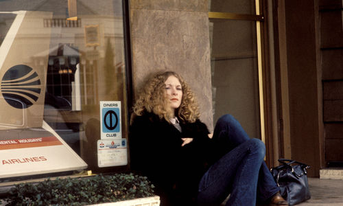 Still from the film Dusty and Sweets McGee (1971) showing a woman seated on the sidewalk, leaning against a building