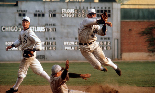 Still from the film Eight Men Out (1988) showing a baseball player slide into a base while another player, on the White Sox team, jumps and throws a ball to complete a double-play while a third player looks on