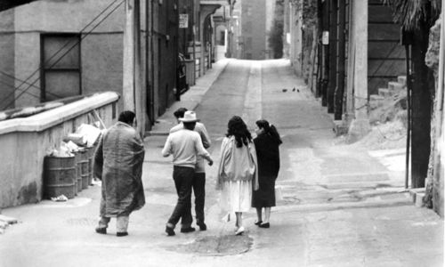 Still from the film The Exiles (1961) showing a group of people walking down an alley