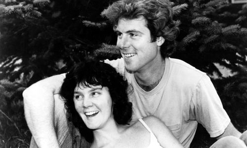 Still from the film Return of the Secaucus Seven (1979) showing a woman leaning against a man, both seated and smiling