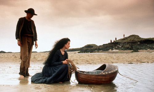 Still from the film The Secret of Roan Inish (1994) showing a woman crouching in the water, over a floating bassinet , with a man standing nearby