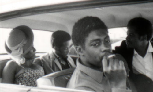 Still from the film Several Friends (1969) showing four people in a car with the man in the foreground smoking a cigarette