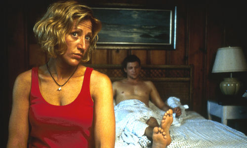 Still from the film Sunshine State (2002) showing a woman sitting in the foreground at the edge of a bed, and a man half-covered by a sheet sitting up against the headboard