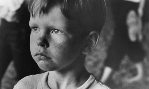 Still from the film Little Fugitive (1953) showing a close-up of a young boy frowning