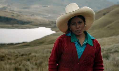 A woman stands outside against a hilly, green landscape with a lake  or river in the background. The woman wears a large, white cowboy hat and wears a red cardigan over a blue shirt.