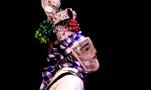 A masked dancer with tall headdress viewed in profile