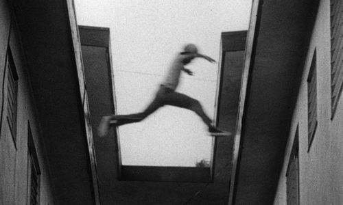 Still from the film Killer of Sheep (1978) showing a boy leaping from one rooftop to another