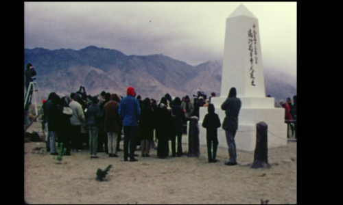 Still from the film Pilgrimage showing a group gathered around a monument built at a former WWII concentration camp for Japanese Americans