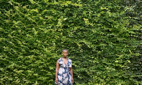 A woman in a dress stands facing the camera  in front of a wall of plants