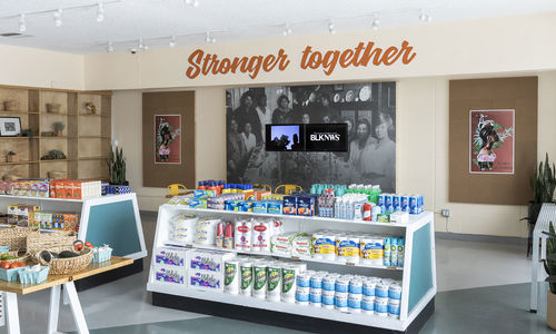 "Photograph showing inside of a grocery store, with low shelving. On the back wall the words ""Stronger Together"" are written in orange cursive. Below this a black and white photographic mural, with two video monitors mounted over top."