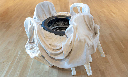 A sculpture of several white plastic chairs covered in a sheet, surrounding a tire