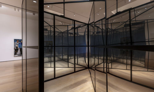 Looking inside a large, mirror-like cube with intersecting walls inside