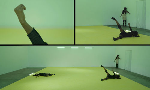 A rectangular image is divided into three segments. The bottom segment spans the full width  and depicts three figures wearing dark clothes in a room with a yellow floor. Two figures lie on the floor and the third stands against the back wall. On the upper left, an arm extends into the frame, with the hand lightly cupped. The image in the upper right shows an detail of the image at bottom, showing the two figures on the right end of that image.