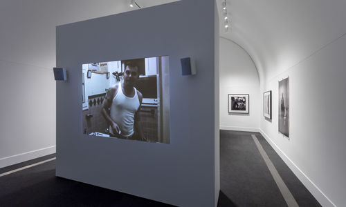 A white gallery with a free-standing wall standing in the foreground. A projection of a color image is visible on the free-standing wall. Three black and white photographs are visible on the gallery walls to the right in the background.