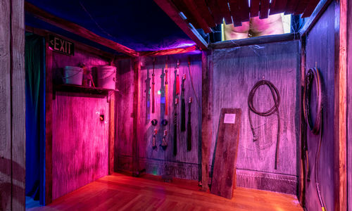 The corner of a room in a haunted house, with whips hanging on a wall lit in purple lighting
