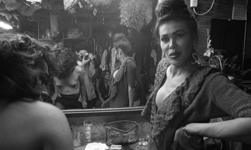A woman in makeup looks over her shoulder with a mirror behind her, the photographer visible in the mirror