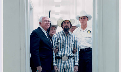 Men stand in a white doorway, all wearing white cowboy hats. The man in the center foreground wears a striped outfit and is bearded. A man in the background holds a shotgun.