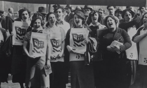 "Black and white photo shows a crowd of women standing, facing the camera, with their mouths open as if shouting. Many women in the foreground hold papers against their chests that have a graphic of a flag with ""All Out May 1"" written on the flag."