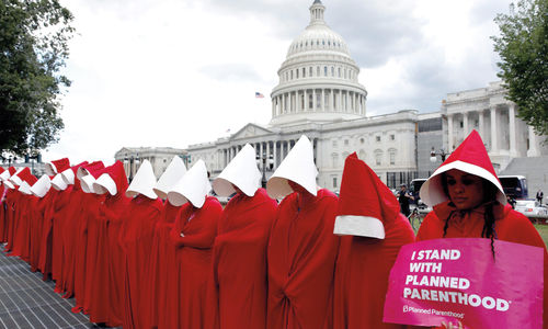 "Women dressed as handmaids from the novel, film, and television series ""The Handmaid's Tale"" demonstrate against cuts for Planned Parenthood in the Republican Senate healthcare bill at the U.S. Capitol in Washington, U.S., June 27, 2017. REUTERS/Aaron P. Bernstein."