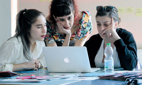 Three women look over a laptop together